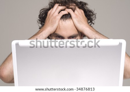 man looking at computer in desperation - stock photo