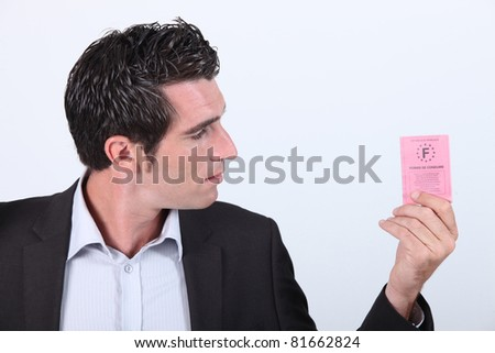 Man looking at driving licence - stock photo