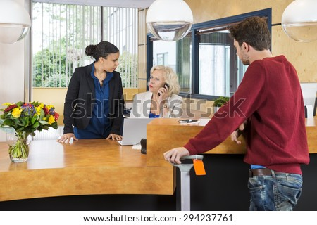 Man looking at female receptionists discussing at counter in hotel - stock photo