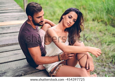 Man looking at his girlfriend sadly while she is fixing her hair. Sunset scene - stock photo