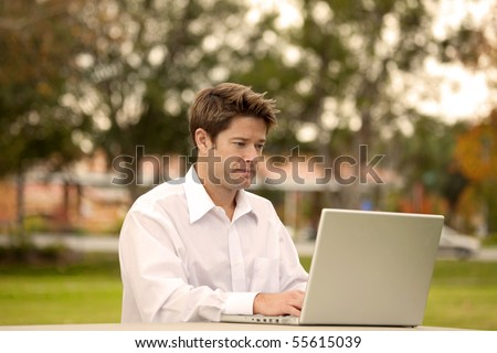 Man looking at his laptop outside - stock photo