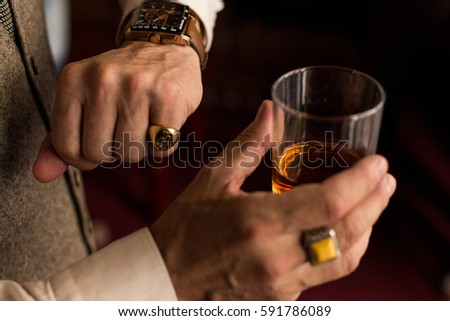 Man looking at his watch on the left hand with a ring on the little finger. In right hand he holding a glass of whiskey.
