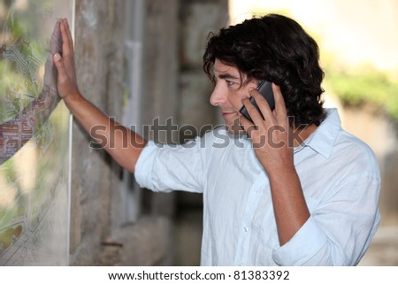 Man looking at map on wall - stock photo