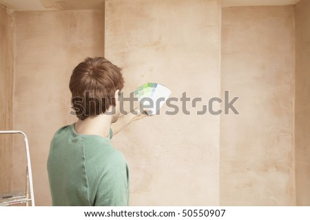 Man looking at paint colour swatches in unrenovated room, back view - stock photo