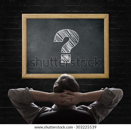 Man looking at question mark on blackboard - stock photo