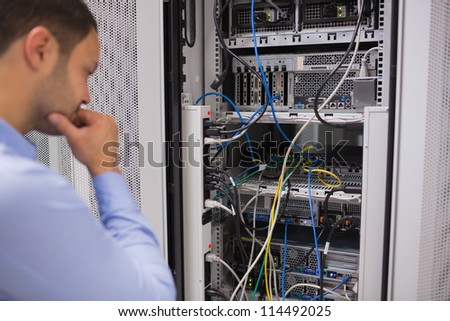 Man looking at rack mounted servers in data centre - stock photo