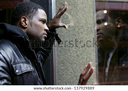 Man looking at reflection in shop window  - stock photo