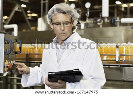 Man looking at tablet PC while working in bottling factory - stock photo