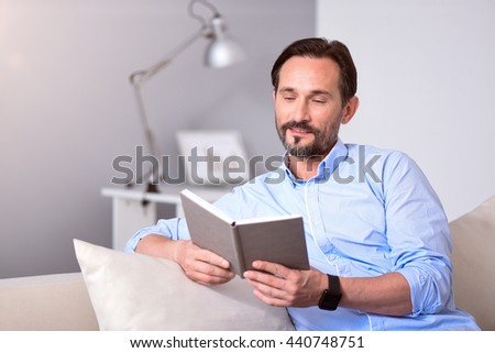 Man looking at the book while sitting