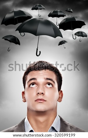 Man looking at umbrellas. - stock photo