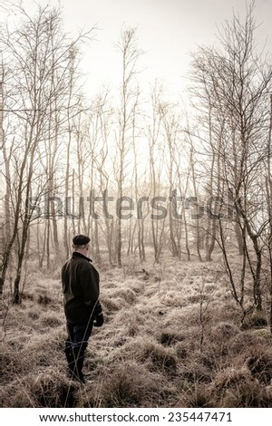 Man looking at winter forest - stock photo