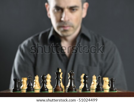 Man looking at wooden chess board thinking about first move - stock photo