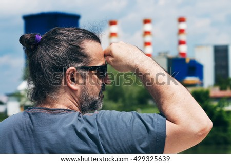 Man looking away into the distance, at the red and white plant chimneys in the background.