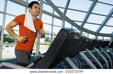 Man looking away while exercising on treadmill in gym - stock photo