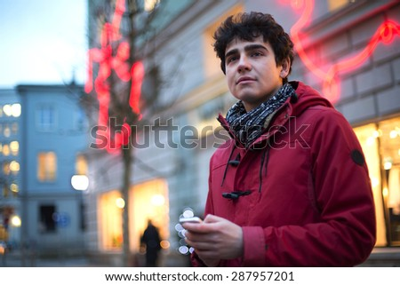 Man looking away while holding cell phone in city during winter