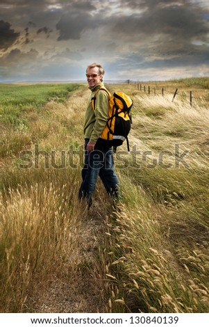Man looking back and smiling on a prairie country road - stock photo