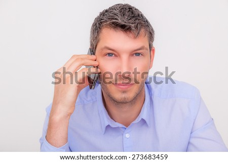 man looking camera while phone on ear