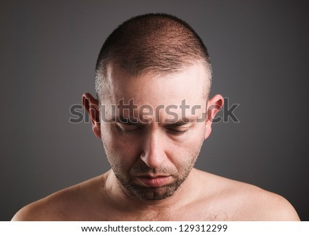 Man looking down isolated on dark background - stock photo