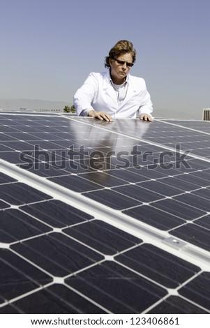 Man looking down on solar power panels - stock photo
