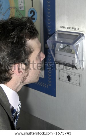 Man looking in ticket machine to see why it didn't give him ticket