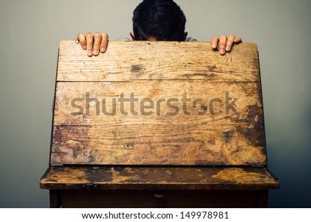 Man looking inside old school desk - stock photo