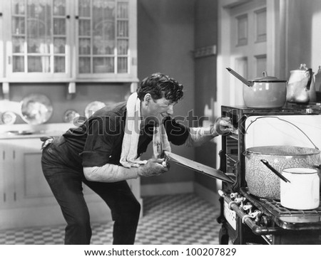 Man looking into oven - stock photo