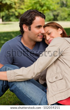 Man looking into the distance as his friend is resting her head on his shoulders with her eyes closed while they both sit on the grass - stock photo