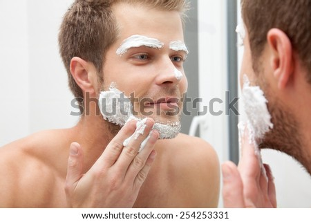 Man looking into the mirror and applying shaving foam - stock photo
