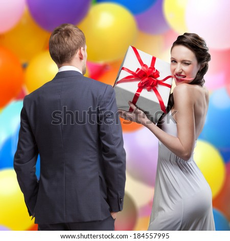 Man looking on smiling woman holding gift - stock photo