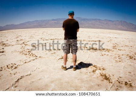 Man looking out over vast salt flat in Death Valley National Park California