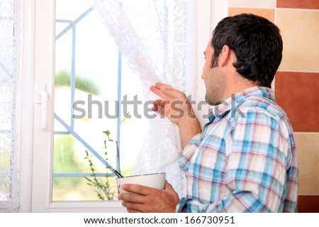 Man looking out window - stock photo