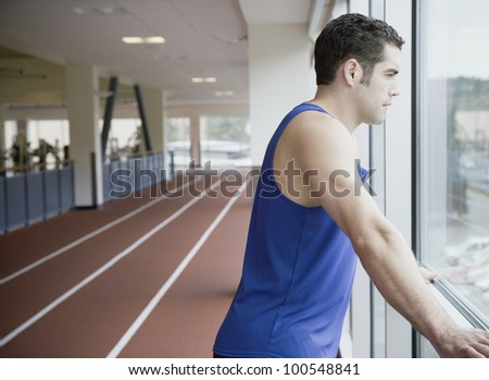 Man looking out window of indoor track - stock photo
