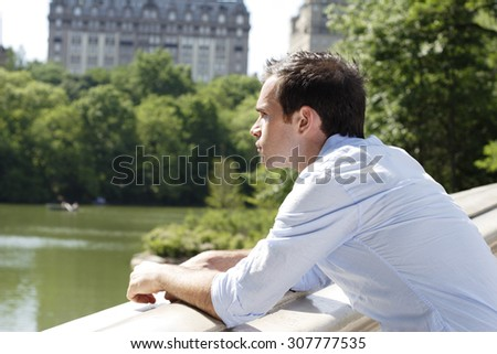 Man looking over the side of a park bridge.