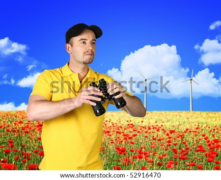 man looking power wind station in red flower field and blue sky - stock photo