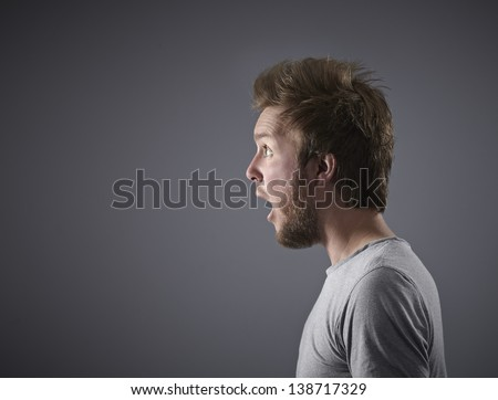 Man looking Shocked and Amazed. Side on to camera. - stock photo