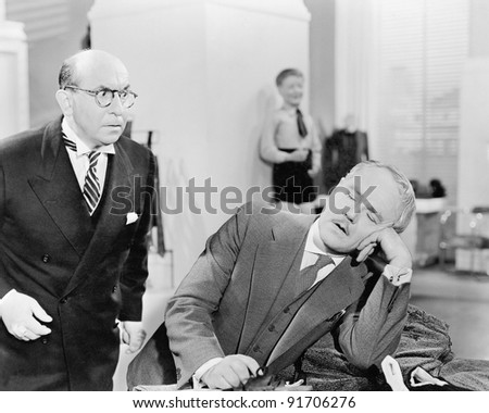 Man looking shocked at a sleeping businessman in the office - stock photo