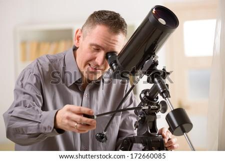 Man looking skyward through astronomical telescope standing near a window - stock photo