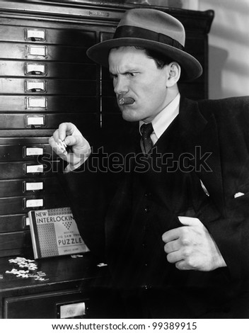 Man looking sternly at a piece of puzzle - stock photo