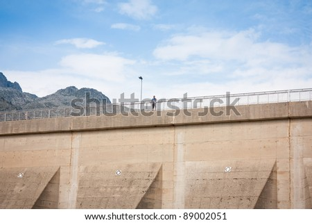 Man looking the views from the top of a lake dam - stock photo