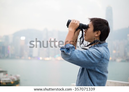 Man looking though binoculars at Hong Kong - stock photo