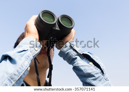 Man looking though binoculars with clear blue sky - stock photo