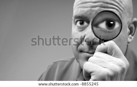 Man Looking Through Magnifier with Huge Eye - stock photo
