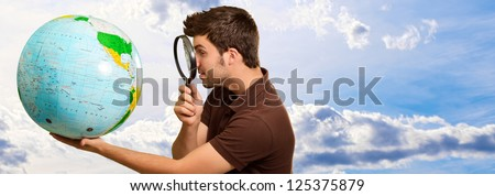 Man Looking Through Magnifying Glass At Globe, Outdoors - stock photo