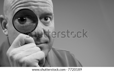 Man Looking Through Magnifying Glass with Big Eye for Humorous Effect - stock photo