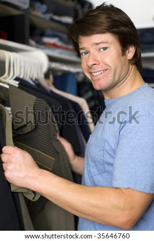 Man looking through shirts in his closet - stock photo