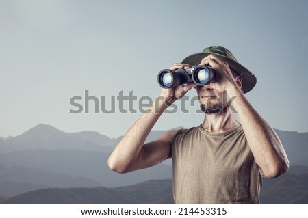 Man looking through the binocular at mountains background - stock photo