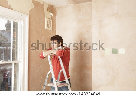 Man looking through window while resting on step ladder in unrenovated room - stock photo