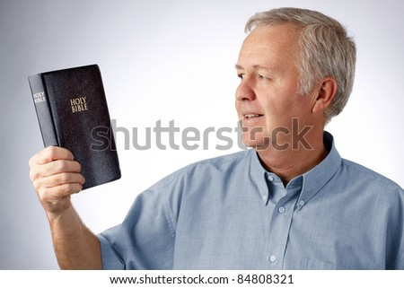 Man looking to the Bible in his hand (Open my eyes that I may see wonderful things in your law Psalm 119.18)