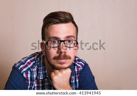 Man looking to the right and dreaming. copy space for a text. hipster in glasses and with beard thinking. - stock photo