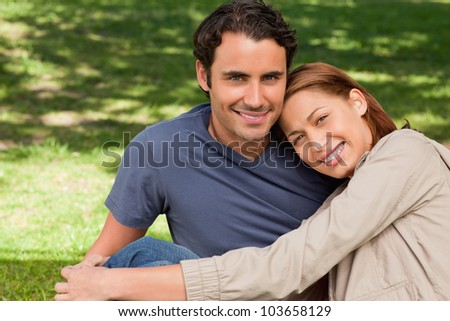 Man looking towards the sky while smiling as his friend rests his rests her head on his shoulder while they lie sit o the grass - stock photo